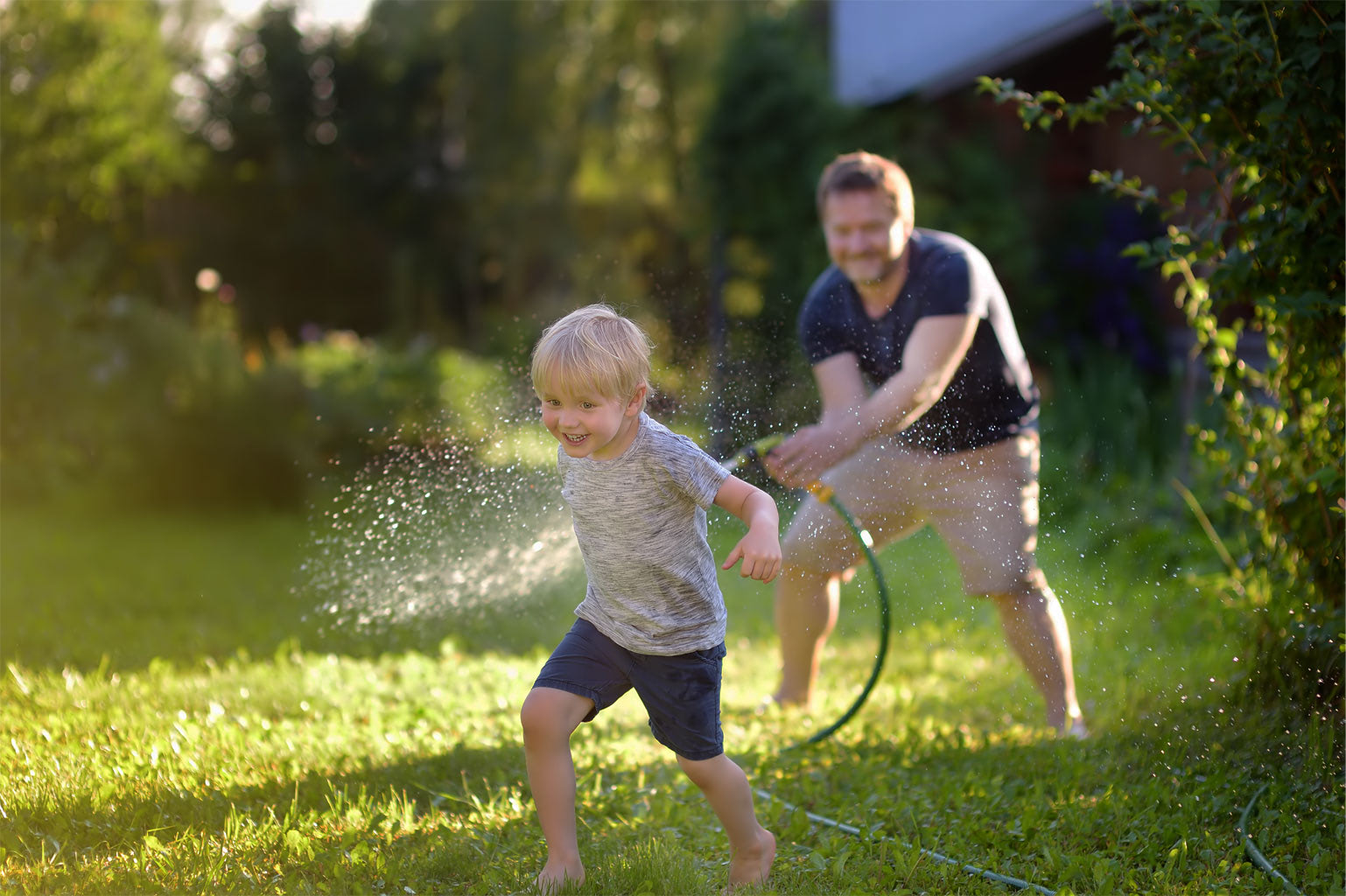 a boy playing in the yard with his father